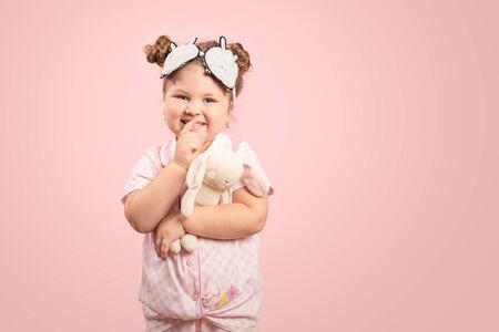 Smiling little child hugging with a toy on pink background.