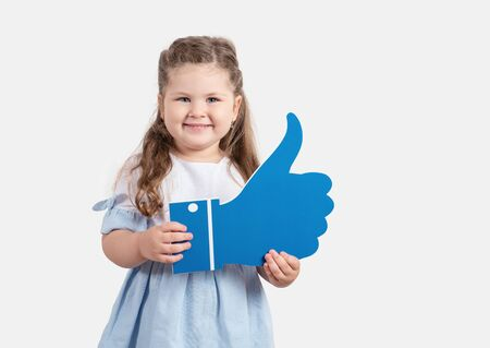 Little cute girl holding cartoon like on grey background.Social media concept
