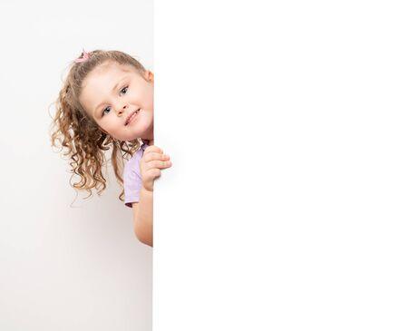 Smiling blue eyed little girl peeking behind a white board. 免版税图像