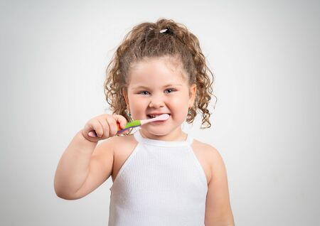 Cute blond girl brushing her teeth on isolated white background