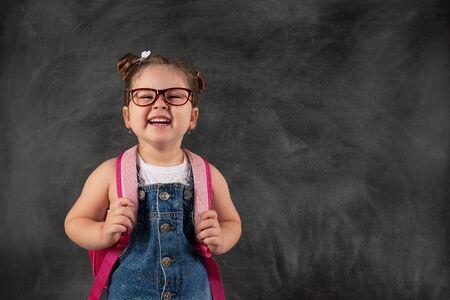 Little cute child holding school bag on blackboard.Education concept Stock fotó