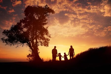 Happy family silhouette standing on against sunset time.