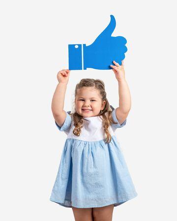 Little cute girl holding cartoon like on grey background.Social media concept. Stok Fotoğraf