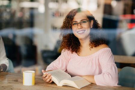 Young woman with eyeglasses reading book in cafe.