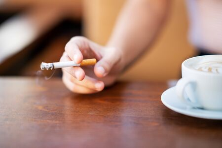 Young woman smoking and holding cup of coffee in a cafe. 版權商用圖片 - 131491990