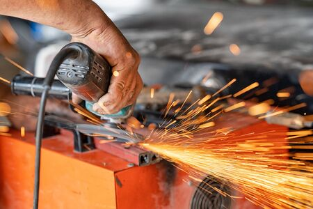 Cutting industrial metal with grinder. Sparks while grinding iron.