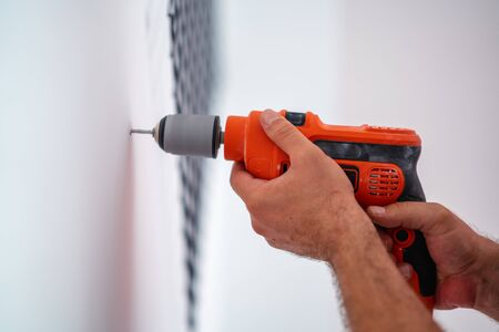 Drilling a hole on the wall for construction or renovation. Imagens