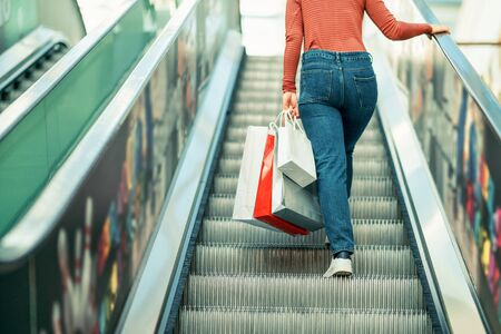 Young woman is walking on the escalator in a mall and shopping.