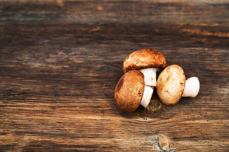 Pile of delicious champignon mushrooms on wooden background. Zdjęcie Seryjne