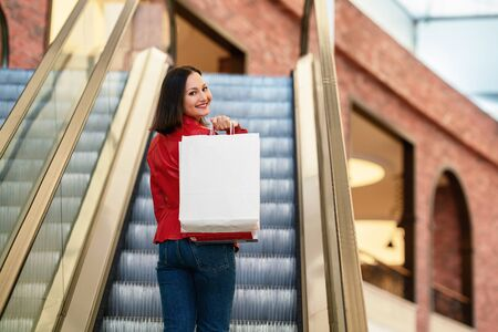 Young woman is walking on the escalator in a mall and shopping with a happy smile. Zdjęcie Seryjne