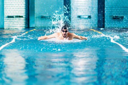 professional swimmer doing exercise in indoor swimming pool.