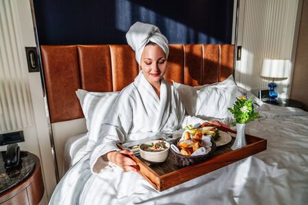 young woman having her breakfast in bed with pleasure.