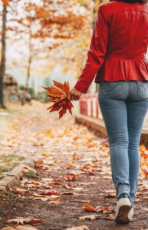 young woman walking on a path in forest enjoing the fall season.