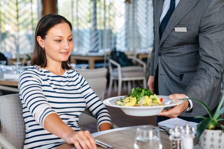 Young woman get served from waiter for a lunch in a elagance restaurant.