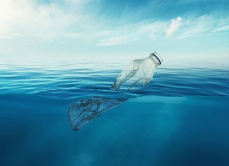 a discarded plastic rubbish bottle floats underwater on a presenting a hazard to all marine life. Stock Photo - 134751522