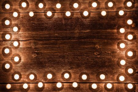Vintage wooden background with tea light candles border.