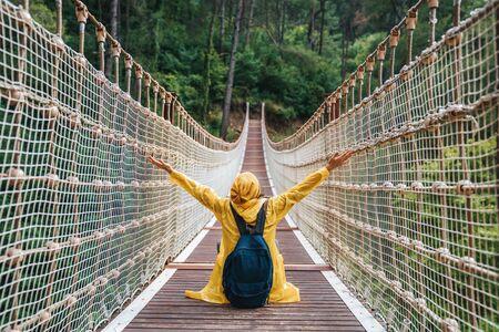Woman hiker with backpack and yellow raincoat sitting on suspension bridge. 版權商用圖片