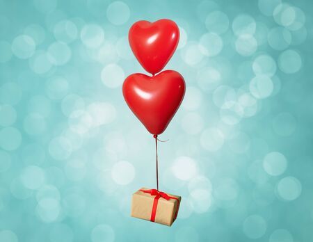 Two heart shaped red air baloon carrying a gift box front of a shiny background. Valentined day and romance concept Stock fotó