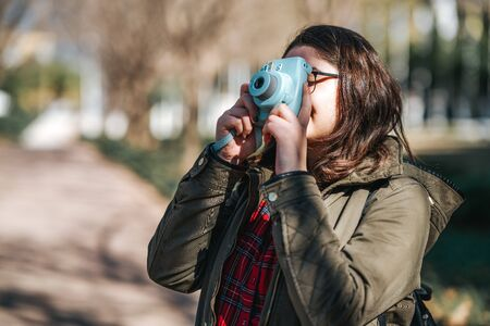 Teenage girl is walking and photographing in her vacation. Tourist, hobby concept