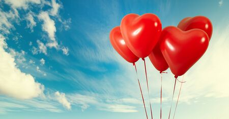 Group of heart shaped red air baloon on blue sky with clouds. Valentines day and romance concept