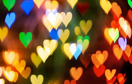 Fondo abstracto, desenfocado y coloreado de luces LED de Bokeh en forma de corazón. Concepto de superposición y banner Foto de archivo
