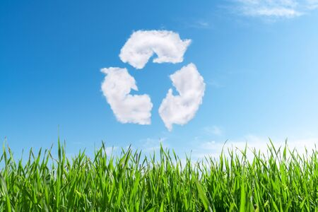 Clouds on the blue sky in shape of the symbol of recycling on green background. Protection nature and future concept  Stock Photo