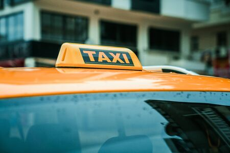 Close up yellow taxi sign on the roof of a car. Transport and travel concept
