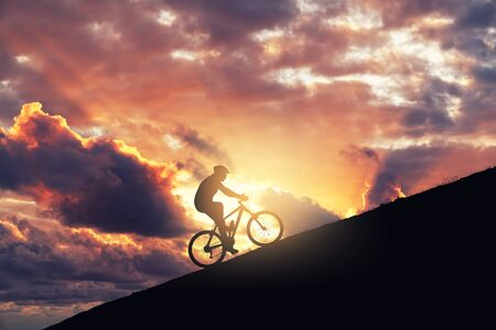 Riding mountain bike on a ramp against cloudy sky. Achieving the difficulty and improvement concept 스톡 콘텐츠