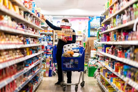 Full shopping cart, customer is stocking vital needs because of global chaos. Shopping with blur supermarket store products, interior background Banque d'images