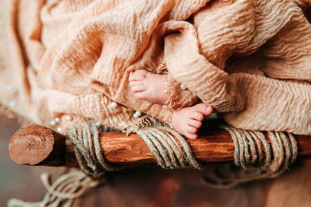 A newborn cute baby sleeping in a vintage wooden cradle with open foot and toes Imagens
