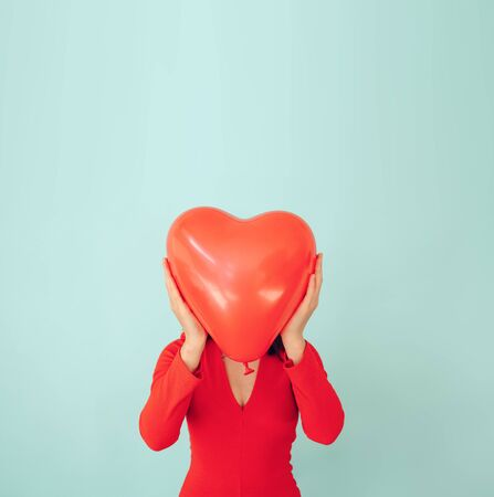 happy woman in love holding red heart shaped balloon. Valentine day and romance concept