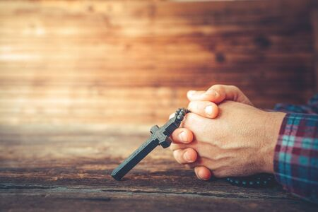 Hands are holding a crucifix and an old hard covered holly Bible and praying on a rustic wooden background