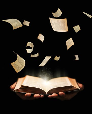 Man is holding book with flying pages and radiance light on black background. learing, reading, knowledge concept