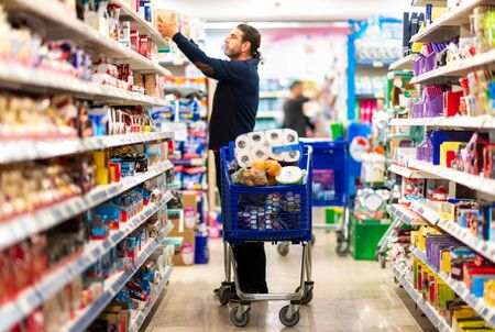 Full shopping cart, customer is stocking vital needs because of global chaos. Shopping with blur supermarket store products, interior background