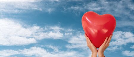 Woman is holding red heart shaped balloon to the cloudy blue sky background. Valentine day and romance concept