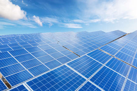 Close up top view of Solar energy panels with blue sky with couds background. Clean and renewable energy concept for a sustainable ecosystem