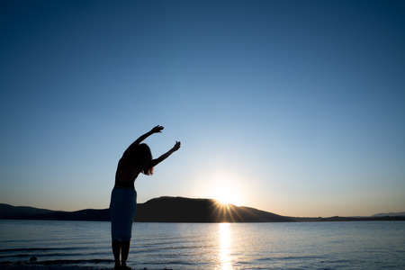Silhouette of young Woman is stretching her body for morning sport or meditation, against the beautiful nature. Health and Tourism concept.