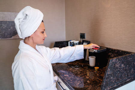 Young woman prepering cup of coffee in the morning in hotel room or home. High quality photo Archivio Fotografico