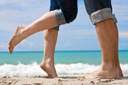 human toe: legs of kissing couple on beach