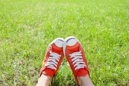 yaşam tarzı: Yeşil çimen üzerinde spor ayakkabı Ayaklar Stok Fotoğraf