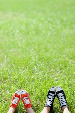 lacing sneakers: Friendly couple in sneckers on green grass Stock Photo