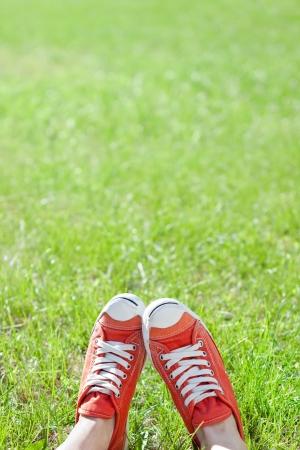 Füße in Turnschuhen auf grünem Gras Standard-Bild - 15347995