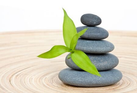 Stone tower on a wooden board with green bamboo leaf Stock Photo - 15408140