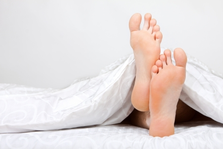 sleep well: Close up of two feet in a bed
