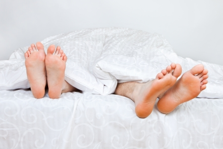 The bared heels of pair in stick out from under bed-sheets Stock Photo