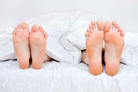 Close up of four funny feet in a bed