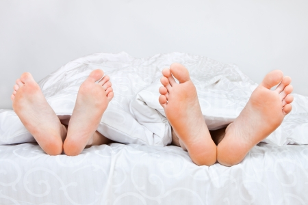 feet naked: The bared heels of pair in stick out from under bed-sheets Stock Photo