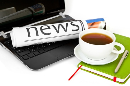 Coffee cup with laptop and newspaper