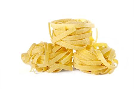 Raw pasta nests on white