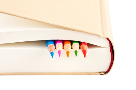 colorful pencils on closed book photo